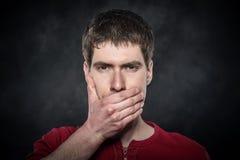 Boca asustada jóvenes de la cubierta de la mano del hombre Foto de archivo libre de regalías