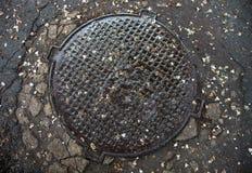 Boca con la cubierta del metal en la superficie agrietada del asfalto Imagenes de archivo