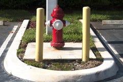 Boca de incêndio de incêndio vermelho no lote de estacionamento com pólos da segurança fotos de stock