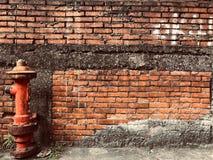 Boca de incêndio de fogo na frente da parede de tijolo vermelho fotografia de stock royalty free