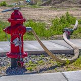 Boca de incendios roja con la manguera conectada con el mercado imagen de archivo libre de regalías