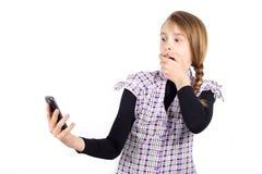 Boca de la cubierta de la muchacha con la mano y mirada del teléfono con la expresión sorprendida Fotos de archivo libres de regalías