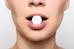 Boca de la mujer de la belleza con los labios y la píldora rojos de la medicina Fotos de archivo