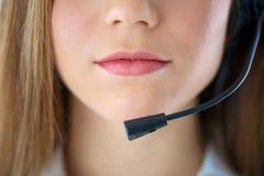 Boca de la mujer que habla en auriculares Foto de archivo