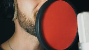 Boca del cantante de sexo masculino que canta en estudio de los sonidos Nueva canción de la grabación irreconocible del hombre El almacen de metraje de vídeo