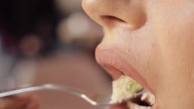 Boca do close-up da mulher com fome adorável que come o sanduíche apetitoso que aprecia o alimento vídeos de arquivo