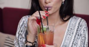 Boca do close-up do modelo fêmea da forma que bebe o cocktail fresco usando a palha que guarda o vidro pelas mãos video estoque