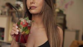 Boca do close-up do modelo fêmea da forma que bebe o cocktail fresco usando a palha que guarda o vidro pelas mãos vídeos de arquivo