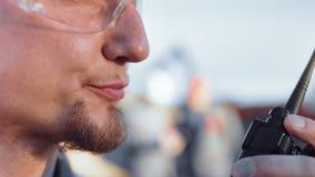 Boca extrema del primer del trabajador de construcci?n de sexo masculino barbudo que habla usando vista lateral del Walkietalkie almacen de metraje de vídeo