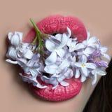 Boca femenina atractiva con la lila fotos de archivo
