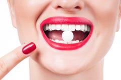 Boca femenina con los labios y la píldora rojos de la medicina Imagen de archivo