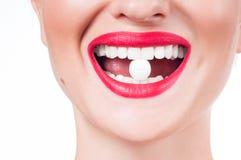 Boca femenina con los labios y la píldora rojos de la medicina Foto de archivo