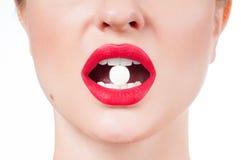 Boca femenina con los labios y la píldora rojos de la medicina Fotografía de archivo