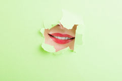 Boca femenina hermosa que muestra una sonrisa a través de la cartulina rasgada Imagen de archivo