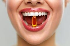Boca hermosa de la mujer con la píldora en dientes Muchacha que toma las vitaminas imagenes de archivo