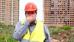 Boca hermosa joven de la cubierta del hombre del constructor en emplazamiento de la obra almacen de metraje de vídeo