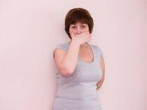 Boca madura de la cubierta de la mujer del retrato con la mano fotos de archivo