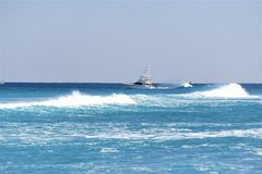 Fishing Yacht makes its way out of the Boca Raton Inlet and on to the fishing grounds. The Boca Raton Beach benefits from great waves which bring out the Stock Photo