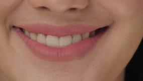 Boca sonriente de la mujer con los grandes dientes blancos cerca para arriba almacen de metraje de vídeo