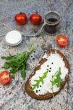 Bocadillo abierto sano con queso fresco con arugula, el tomate y la pimienta Imagen de archivo