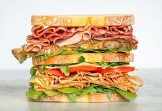 Bocadillo acodado doble fresco con el jamón, lechuga, tomates, queso en un pan de la tostada Fondo del alimento imagenes de archivo