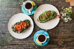 Bocadillo con el aguacate y otro bocadillo con tocino y el tomate al lado de dos tazas de té en una tabla de madera Imágenes de archivo libres de regalías