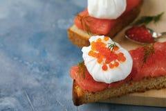 Bocadillo con el huevo - escalfado, el caviar y los pescados rojos Foto de archivo libre de regalías