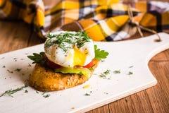 Bocadillo con el huevo escalfado y el tomate en una tabla de cortar Fotos de archivo
