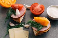 Bocadillo con el jamón, los tomates y el queso imagenes de archivo
