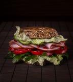 Bocadillo con el jamón, verdes, tomates, pan con los granos en el wo Foto de archivo