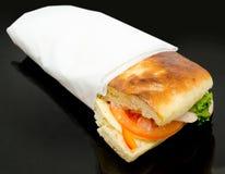 Bocadillo con el jamón y el queso envueltos en servilleta Imagen de archivo