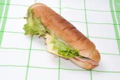 Bocadillo con el jamón y la ensalada en un mantel verde Foto de archivo libre de regalías