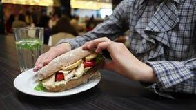 Bocadillo con el pollo y las verduras en una placa Primer de la mujer que come en café metrajes