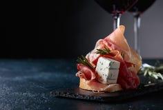 Bocadillo con el prosciutto, el queso verde y el romero Imagen de archivo