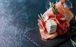 Bocadillo con el prosciutto, el queso verde y el romero Imagen de archivo libre de regalías