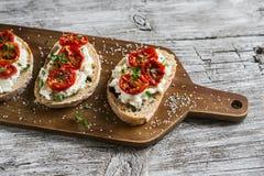 Bocadillo con el queso de cabra, los tomates secados al sol y el tomillo, servidos en el tablero Fotos de archivo