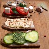 Bocadillo con el queso feta, tomates, aceitunas negras, setas, Cu Imágenes de archivo libres de regalías