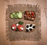 Bocadillo con el queso feta, tomates, aceitunas negras, setas, Cu Imagenes de archivo