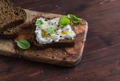 Bocadillo con el queso suave, el aceite de oliva y la albahaca, servidos en tabla de cortar verde oliva en superficie de madera o imágenes de archivo libres de regalías