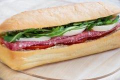 Bocadillo con el salami, la mozzarella, el arugula y tomates Fotos de archivo libres de regalías