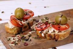 Bocadillo con el tomate, el queso blanco y las aceitunas en una tabla de madera Imagen de archivo