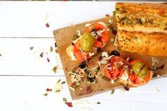 Bocadillo con el tomate, el queso blanco y las aceitunas en una tabla de madera Foto de archivo