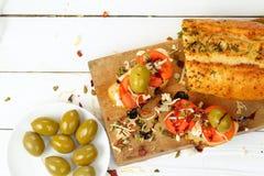 Bocadillo con el tomate, el queso blanco y las aceitunas en una tabla de madera Imágenes de archivo libres de regalías