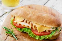 Bocadillo con el tomate y el pollo asado a la parrilla queso Foto de archivo