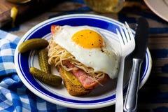 Bocadillo con la chucrut, el jamón y los huevos fritos Imagen de archivo