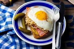 Bocadillo con la chucrut, el jamón y los huevos fritos Foto de archivo libre de regalías