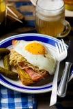 Bocadillo con la chucrut, el jamón y los huevos fritos Foto de archivo
