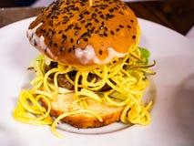 Bocadillo con la hamburguesa de la carne de vaca y las porciones de fritadas fotografía de archivo libre de regalías