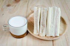 Bocadillo con leche en el fondo de madera Fotografía de archivo