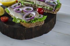 Bocadillo con los arenques salados, la mantequilla y la cebolla roja en vieja tabla de cortar rústica Foco selectivo foto de archivo
